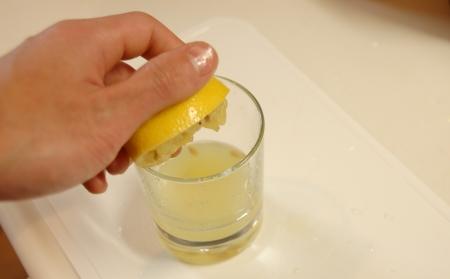 水にレモンを絞りいれる